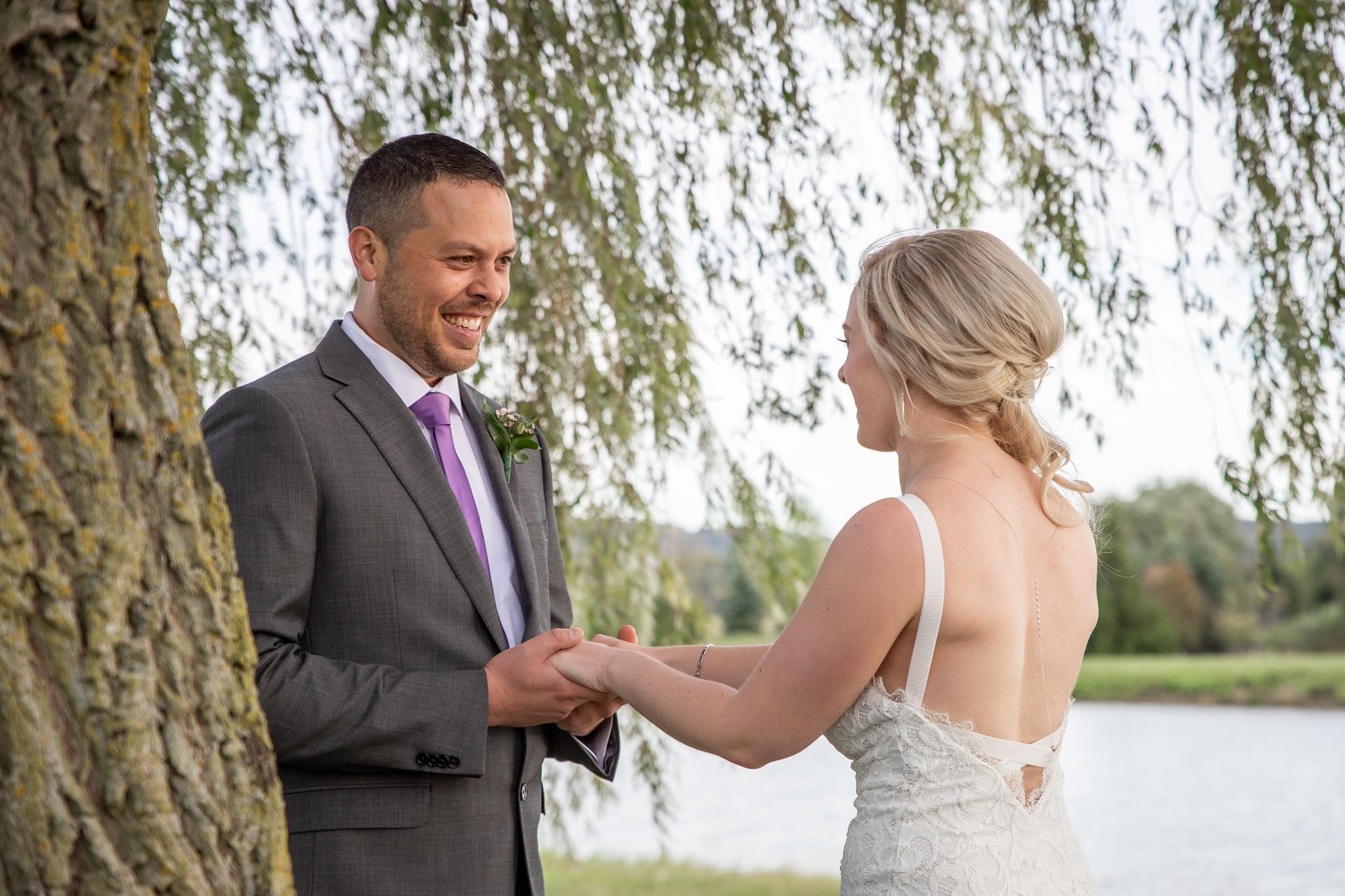 groom holds his bride's hands