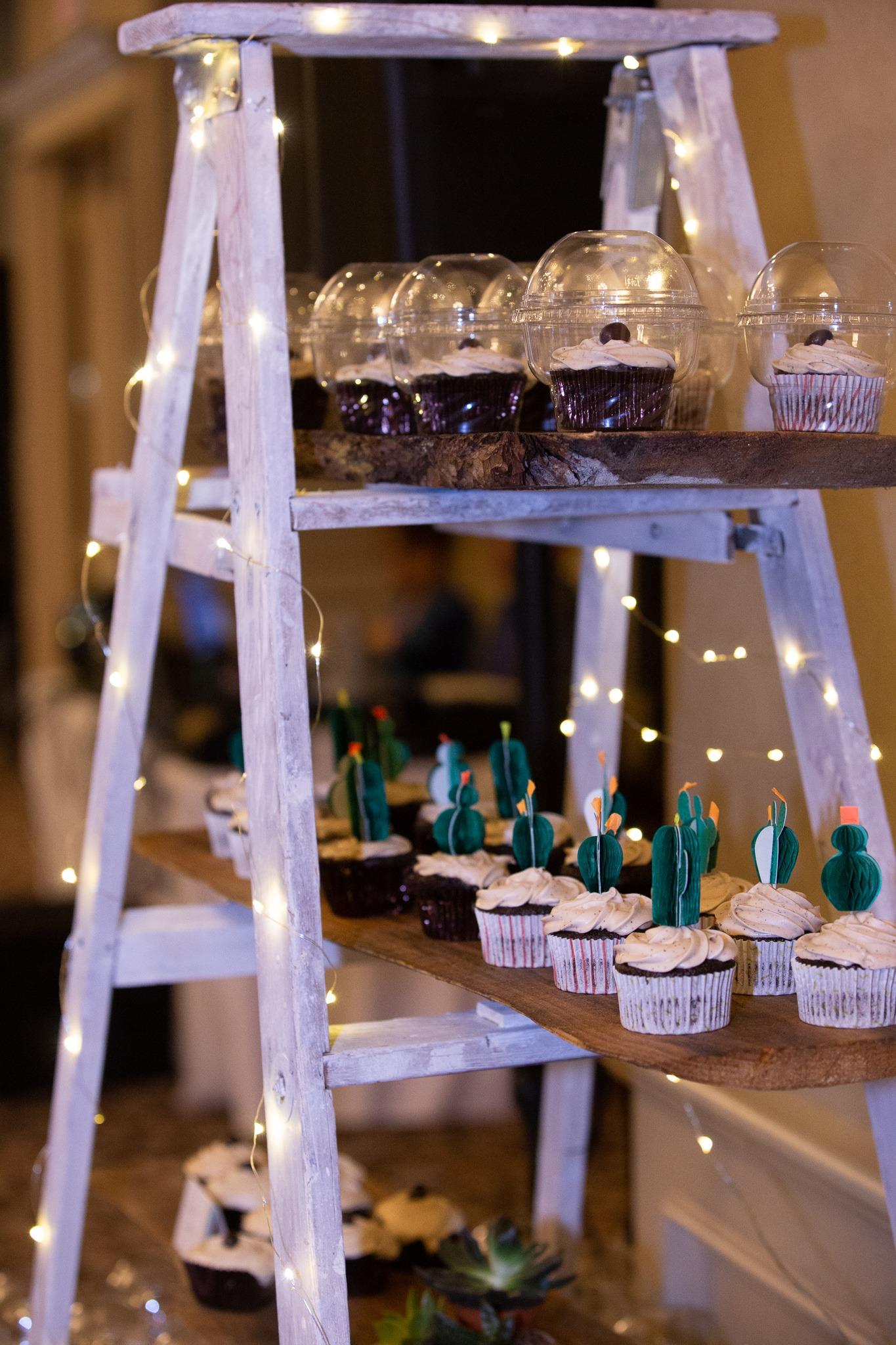 wedding desserts on a decorative ladder with lights