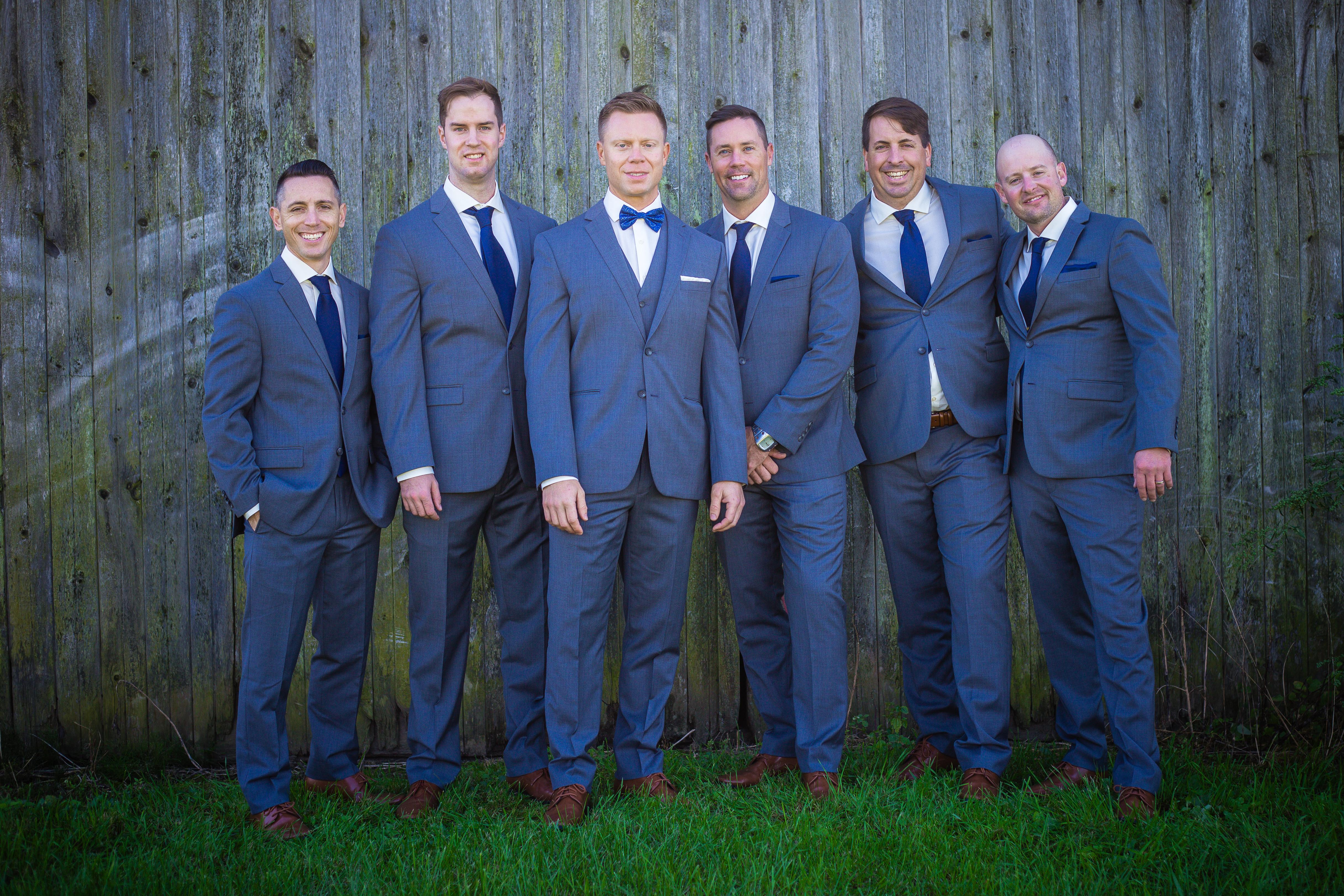 groomsmen dressed in navy blue suits
